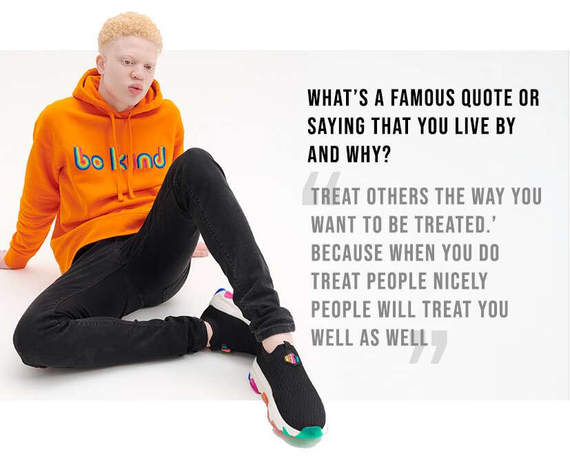 Shem modelling the orange Be Kind Hoodie